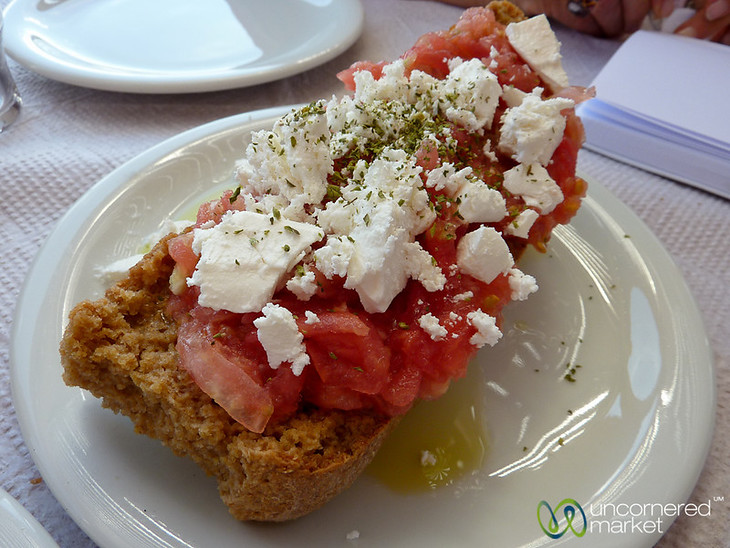 A delicious slice of dakos (dried bread topped with tomatoes, cheese and olive oil) at Seli Ambelou Tavern near Venetian windmills on Crete, Greece.